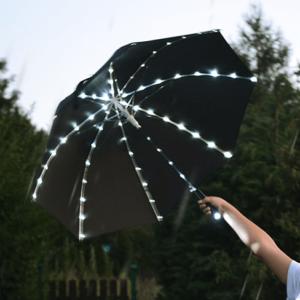 Parasol z drutami oświetlanymi żarówkami LED.